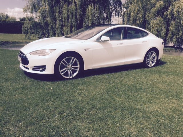 Tesla side view with wheel alloys on display in field