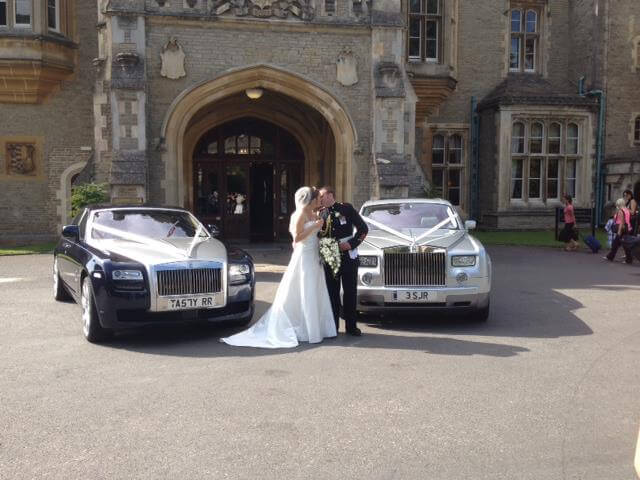 couple kissing in front of church with two rolls royce vintage and classic cars for wedding