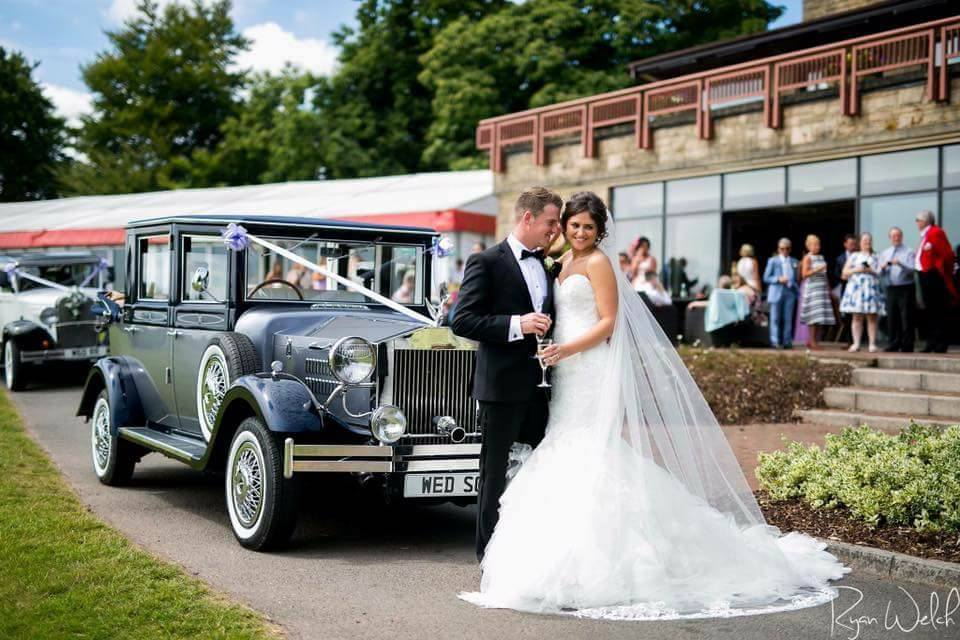 Newly wed couple next to vintage viscount car